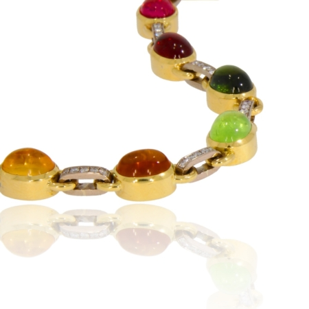 Close up of sweetie bracelet in 18ct gold with nine oval cabochons in a variety of gemstones
