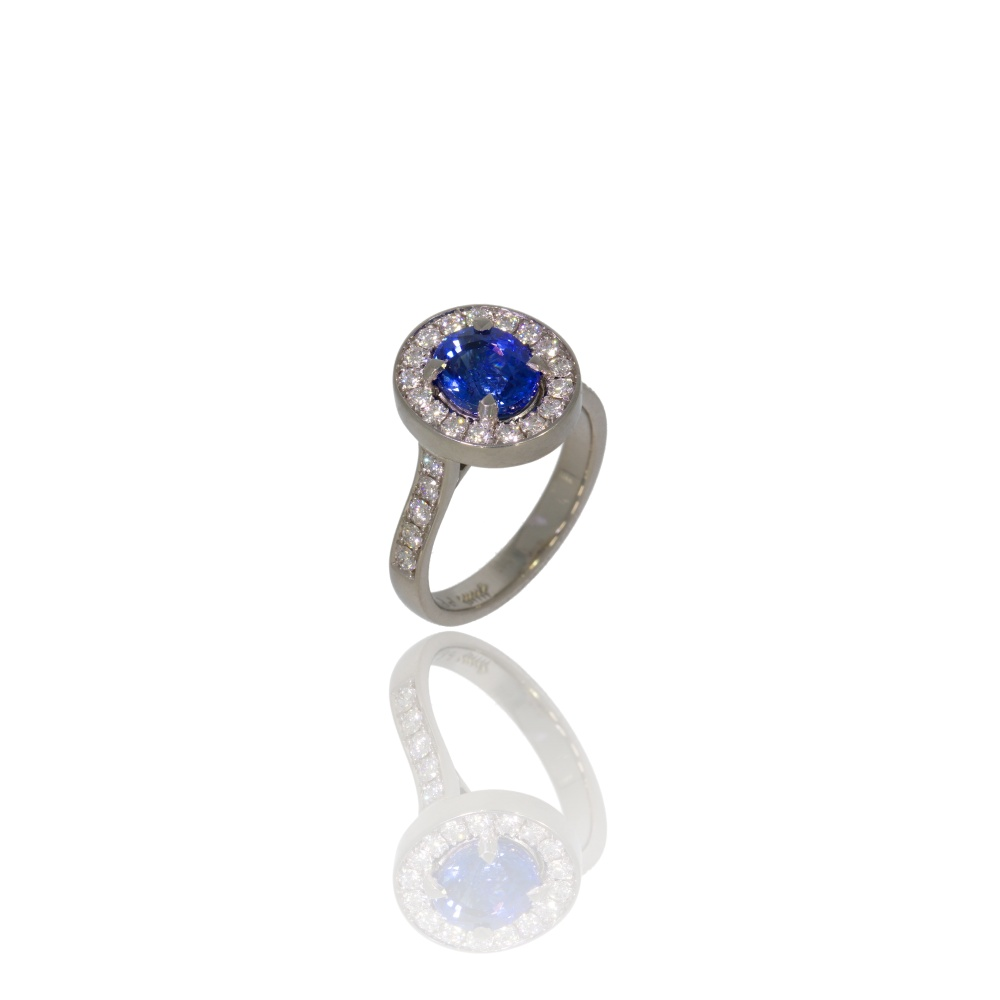 Platinum ring with oval ceylon sapphire and a halo of diamonds.