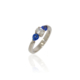 Three stone palladium ring with a central claw set brilliant diamond and two claw set pear shaped sapphires