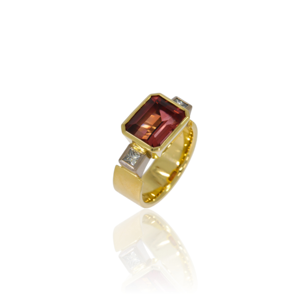 Three stone gold ring with an emerald cut tourmaline framed by two princess cut diamonds.